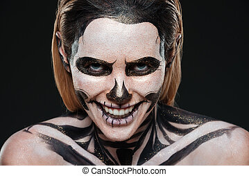 Smiling young woman with skeleton halloween makeup laughing...