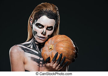Woman with skeleton halloween makeup holding pumpkin over...
