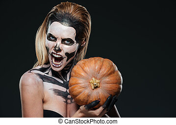 Woman with scared gothic makeup holding pumpkin and shouting...