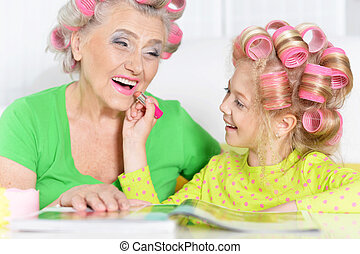Senior woman and granddaughter doing make up at home