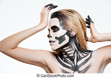 Woman with scared halloween makeup standing and posing over...