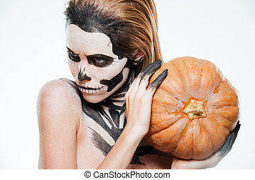 Portrait of girl with fearful halloween makeup holding...