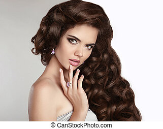 Brunette girl with long shiny wavy hair Beauty makeup...