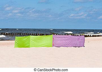 beach windbreak - colorful textile beach windbreak stuck in...