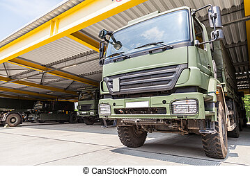 military truck stands under military roof