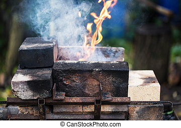 flame in outdoor rural brick forging furnace during coal...