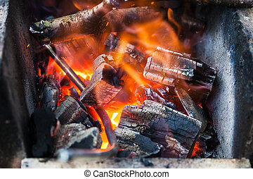iron rod is heated in burning wooden coals in the forge...