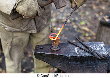Blacksmith cut out a buckle with hammer and chisel on anvil...