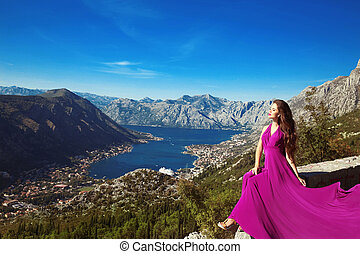 Romantic Woman in blowing dress above Landscape of mountain...