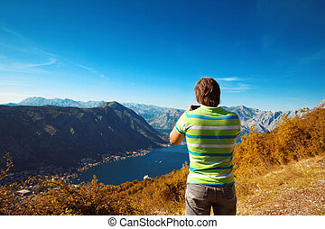 Kotor. Montenegro. Back view of young man tourist taking...