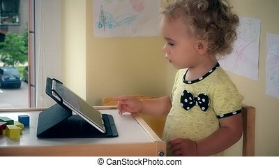 Serious child using tablet computer sitting near table.