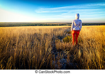 Young beautiful lean girl wears red pants and white hoodie stays in a field among golden grass at sunset, back to camera, facing the sun. Blue sky with thin clouds on background. Travel photography