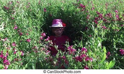 The girl child is playing in the tall grass in the meadow. On the meadow grew grass thick and lots of flowers. Girl hiding in the grass.