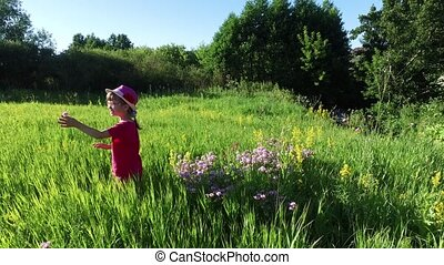 Girl child walks on a meadow. The girl collects wild flowers. Sunlight glistens in the girl's hair.