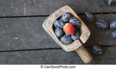 food background, plums and strawberry - Plums on an old...