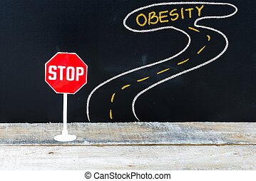Mini STOP sign on the road to OBESITY, hand drawing over...