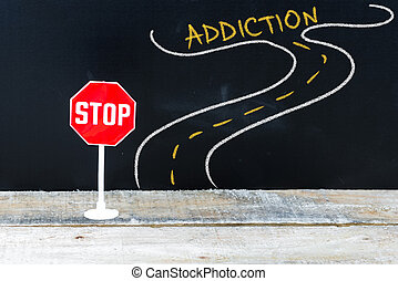 Mini STOP sign on the road to ADDICTION