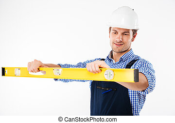 Portrait of a young worker in overalls using level tool