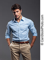 Handsome casual man standing with arms in pockets isolated...
