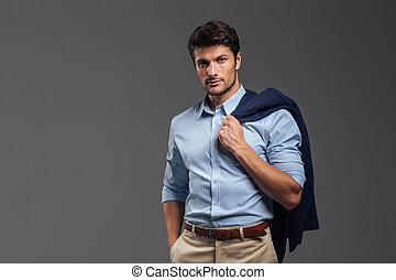 Handsome businessman holding his jacket over shoulder on...
