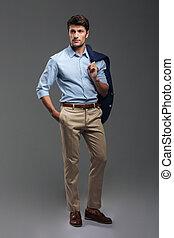 Handsome businessman holding his jacket over shoulder with...