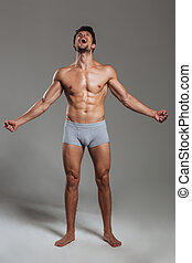 Full length portrait of a handsome muscular man shouting...