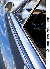 Details of a car body - Mirror and window of a car parked in...