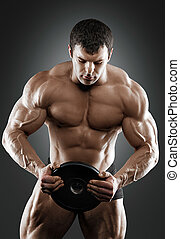 Portrait of bodybuilder with dumbbells in his arms on grey...