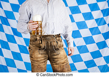 Bavarian man with leather pants Lederhose holds Oktoberfest...