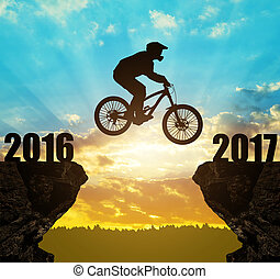 Cyclist jumping into the New Year - Silhouette cyclist...