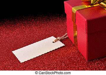 Gift with tag on bright red textured table elevated view -...