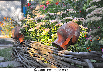 rural scenery - old clay pots on a wattled fence near flowers