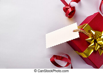 Red gift box with golden ribbon and label hanging