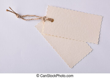 Two beige textured paper tags tied with string - Two beige...
