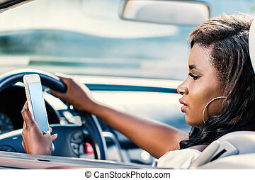 African girl driving car with smart phone in hand.