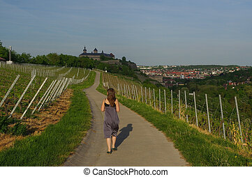 Woman walking on a road with Vineyard landscape view to the...