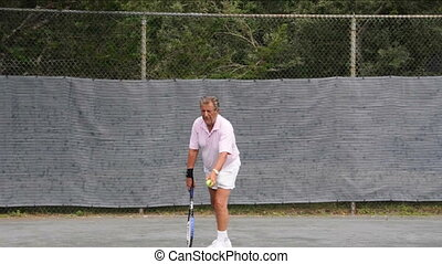 senior practice tennis serve - senior retired active man...