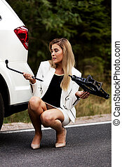 Young woman holding jacke and wheel wrench.