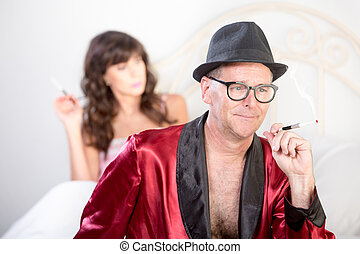 Playboy and Woman in Bed Smoking - Playboy in hat with...