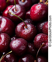 Fresh ripe black cherries on a blue stone background Top view Close up