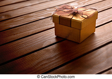 Golden gift box on diagonal table wooden slats elevated view...