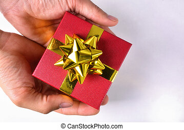 Hands offering a red gift box