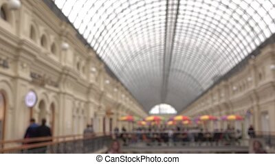 Blurred people walking in shopping mall with glass roof. 4K...