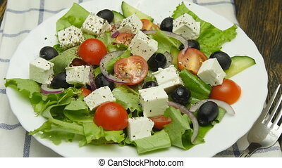 salad with fresh vegetables and feta cheese on wooden table