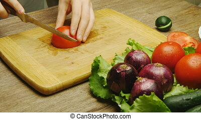 male hand cutting tomato on cutting board with sharp knife -...