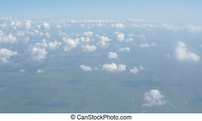 Clouds and sky as seen through window of an aircraft,White...