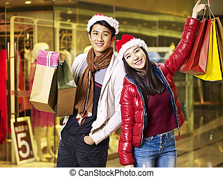 young asian couple shopping for christmas - young asian...