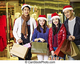 young asian people shopping for christmas - group of young...