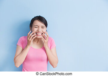 woman have toothache isolatedon blue background, asian