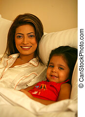 In Bed - Young Mother and daugther in bed - smiling faces